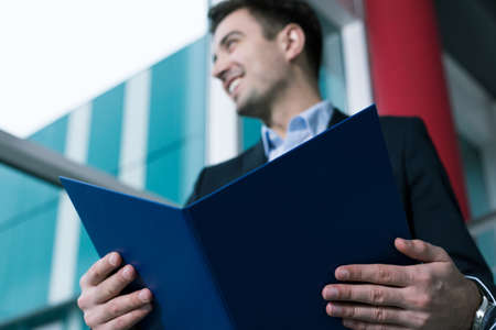 document file: Cheerful elegant man holding an open document file close to the camera