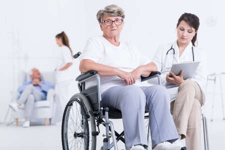cropped shot: Cropped shot of a sad female patient in a wheelchair next to her doctor