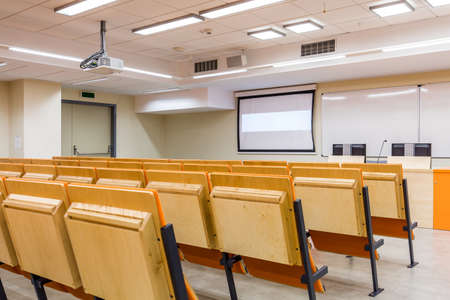 lightsome: Modern space of lecture room with row of chairs, screen and whiteboards