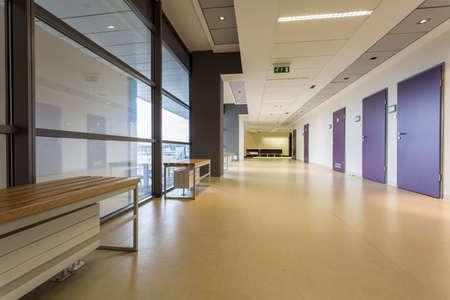 floor covering: Spacious corridor with benches opposite navy blue doors