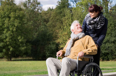senility: Photo of woman supporting elderly man on wheelchair