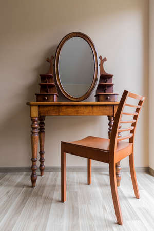 Shot of a wooden antique dressing table with an oval mirror