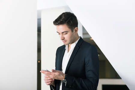 smartly: Close-up of a smartly dressed young man using a mobile phone in office building