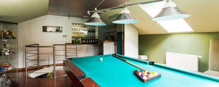 billiards room: Spacious interior with billiard table, stylish lighting and home bar, panorama