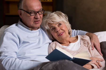 cuddled: Delicate portrait of an elderly marriage cuddled on the sofa while reading a book together Stock Photo