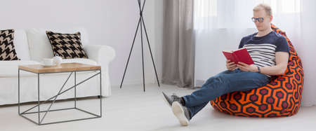 bean bag: Light interior with double sofa, small chair, young man relaxing on a bean bag