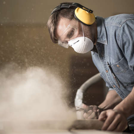 electric saw: Carpenter wearing protective headphones while using electric saw