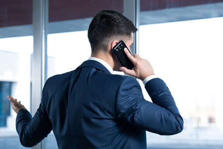 influential: Young, elegant businessman standing back in his office and talking on a mobile phone