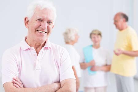 Actieve senior man lachend, groep ouderen op de achtergrond Stockfoto