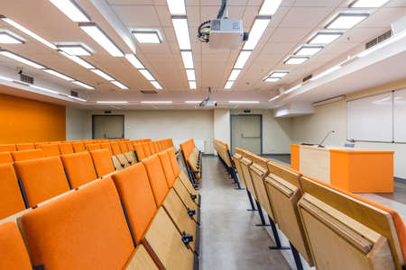 lightsome: View on row of wooden chairs and lecturer desk in the lecture hall decorated with orange accents