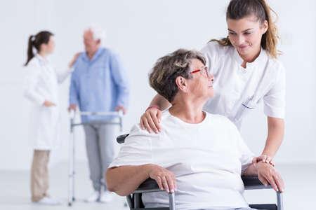 Geernteter Schuss einer jungen Krankenschwester, die um ihrem Patienten in einem Rollstuhl sich kümmert