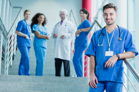 intern: Smiling intern stands in front of the stairs when his colleagues speak with a supervisor Stock Photo