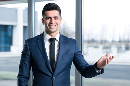 Jonge, elegante zakenman die zich in zijn kantoor en lachend met zijn hand opgeheven in natura gebaar Stockfoto