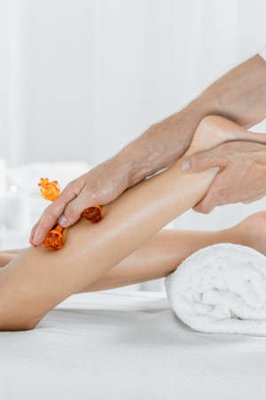 lymphatic drainage therapy: Close up of a womans legs and masseurs hands isolated on a light background