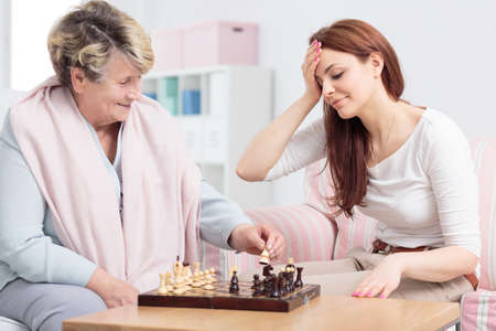 Shot of a senior woman playing chess with her daughter