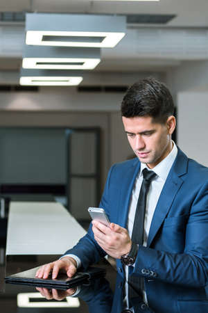 front office: Young, elegant businessman in an office interior, standing close to the front office counter with him mobile phone Stock Photo