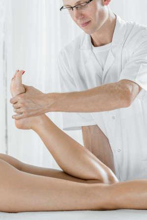lymphatic drainage: Professional masseur doing legs massage, light interior Stock Photo