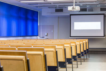 lightsome: Darkened lecture hall with screen and rows of chairs for students