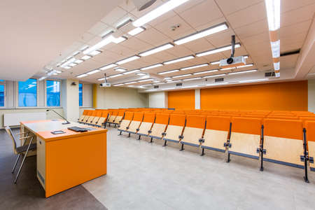 lightsome: Lecture room with a desk and a row of wooden chairs Stock Photo