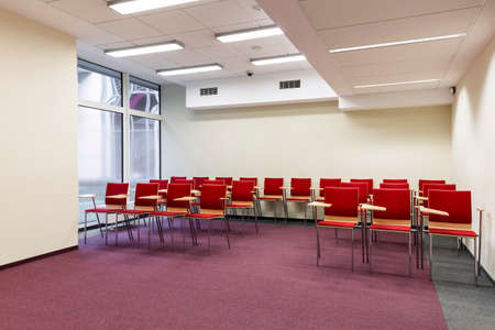 carpet and flooring: Small lecture room with three rows of chairs with desks
