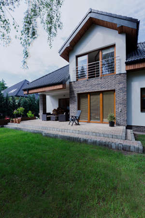 outside house: Shot of a patio made of bricks, surrounded by lots of green