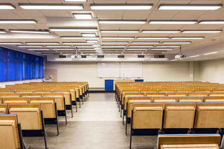 View from the back on rows of wooden chairs and white boards in lecture hall