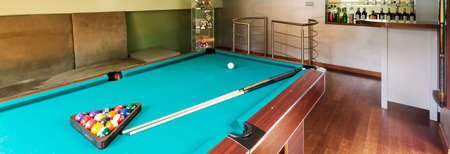 snooker room: Stylish villa interior with pool table and home bar, panorama Stock Photo