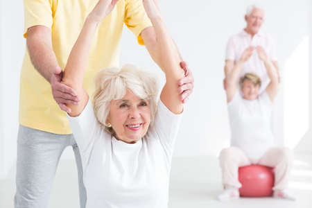 elderly adults: Happy senior woman exercising with group of elderly people, light interior