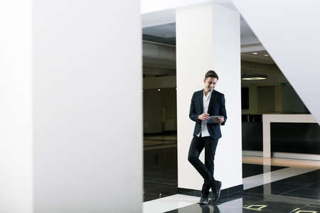 graduation suit: Young smiling man with a tablet standing by the pillar of a modern public building Stock Photo
