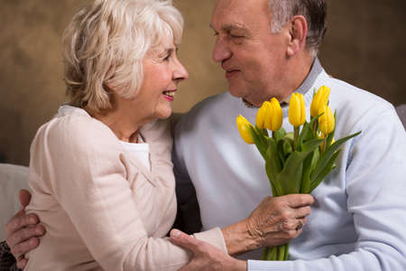 couples hug: Lovely portrait of an elderly man affectionately holding his wife who is holding a bunch of yellow tulips