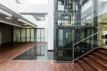 lift: Ground floor of a modern building with glass elevator core in the middle