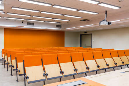 comfort room: Row of wooden chairs in the lecture hall decorated with orange accents