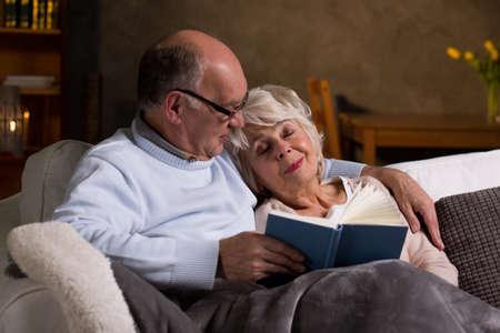 parejas enamoradas: el matrimonio de ancianos sentados en un sofá, leyendo el hombre y la mujer durmiendo en su hombro