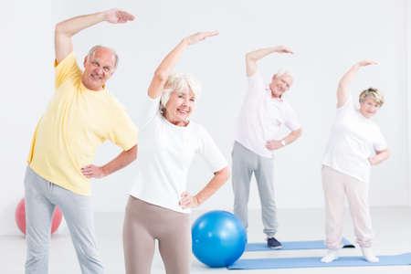actividad fisica: Mayores felices durante la sesión de ejercicios para parejas, la luz y amplio entre
