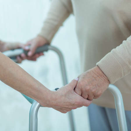 ageing: Close-up of nurse helping disabled elderly lady with a walking frame