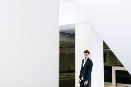 public building: Untypical capture of a young man wearing smart casual clothes, in a modern public building