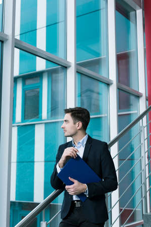 smartly: Young smartly dressed man holding a document file in an office building with a glass wall
