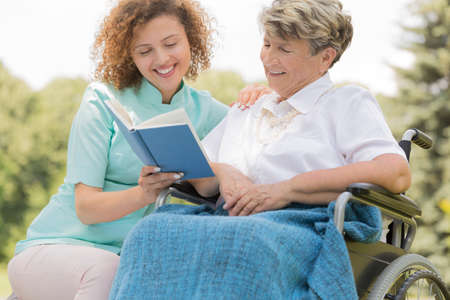 persona de la tercera edad: Cropped shot of a smiling caregiver reading a book to an elderly lady Foto de archivo
