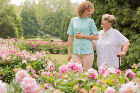 Shot of a happy elderly woman walking with her nurse around the garden Stock Photo