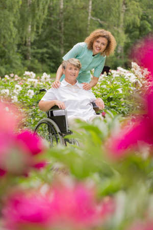 home and garden: Shot of a senior lady in a wheelchair with her caregiver relaxing in the garden