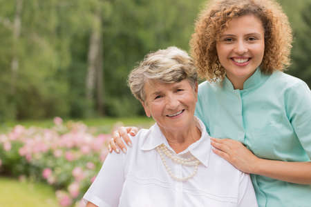 Portait of a young smiling nurse with her senior patient in the park