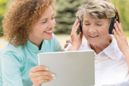 Shot of a young nurse showing something on the screen to retired woman wearing headphones