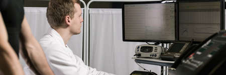 physical test: Strong sportsman on his medical check-up. Young doctor controlling his patients results on computer screen