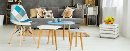 Panorama of a coffee table with a patchwork chair in a modern studio apartment