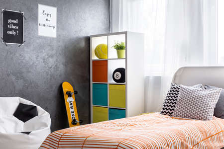 single shelf: Shot of a bedroom interior with a single bed and colorful shelf Stock Photo