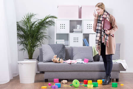 clutter: Frustrated mother in a coat and shoes, talking on the phone in a room filled with cluttered kids items Stock Photo