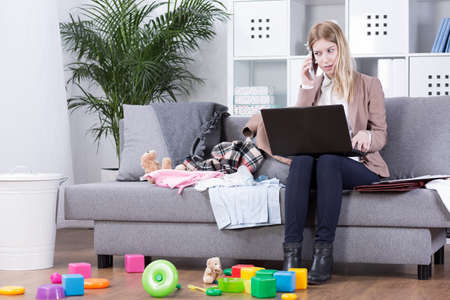 work at home: Young mother in office clothes working on her laptop in the living room among scattered toys