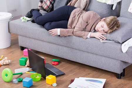 Young mother sleeping in her office clothes on a sofa in a messy living room Stockfoto