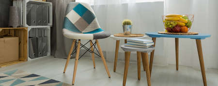 coffee table: Close-up of a coffee table and a patchwork chair in a bright modern living room