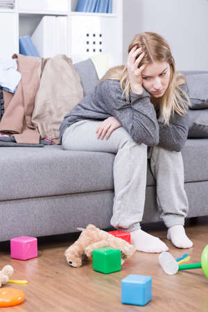 miserable: Miserable young mother sitting on a sofa in a cluttered living room